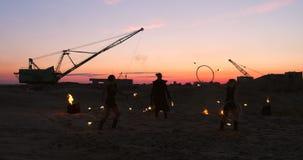 Un grupo de ejecutantes de circo profesionales con el fuego muestra demostraciones de la danza en la cámara lenta usando los lanz metrajes