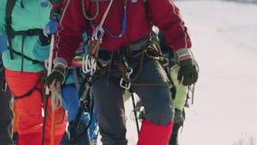 Un grupo de escaladores en su engranaje que caminan encima de la nieve en una cuesta de montaña escarpada almacen de metraje de vídeo