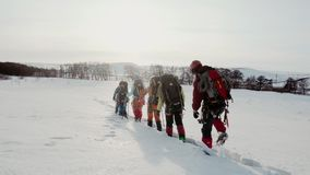 Un grupo de escaladores pasa con confianza con las derivas y los movimientos m?s profundos de una l?nea Detr?s de ellos mochilas  almacen de metraje de vídeo