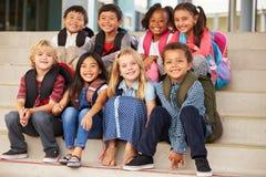 Un grupo de escuela primaria embroma sentarse en pasos de la escuela imágenes de archivo libres de regalías