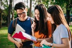 Un grupo de estudiante asiático joven o adolescente en universidad que sonríe y que lee el libro Imagen de archivo