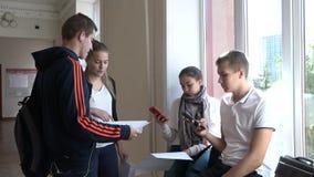 Un grupo de estudiantes discute el proyecto durante una rotura en la universidad metrajes