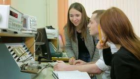 Un grupo de estudiantes que estudian en la universidad como ingeniero Siéntese alrededor de la cabina con el equipo Varias person almacen de video