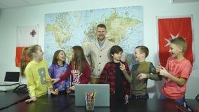 Un grupo de estudiantes que ríen en la sala de clase así como el profesor metrajes