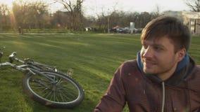 Un grupo de estudiantes que se sientan en el parque en el césped que habla de vida Tres amigos jovenes comunican en el parque metrajes
