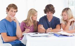 Un grupo de estudiantes que se sientan junto como todos estudian   Imagen de archivo