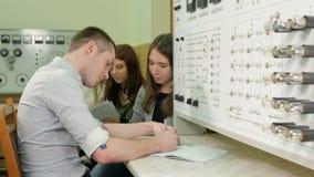 Un grupo de estudiantes que trabajan junto en un laboratorio de la comprobación del banco de pruebas Muchos interruptores y luces metrajes