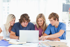 Un grupo de estudiantes utiliza una computadora portátil para contestar a sus preguntas Imagenes de archivo
