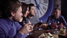 Un grupo de gente joven atractiva en un restaurante moderno en una tabla con bocados y vino Los hombres y las muchachas beben el  almacen de video