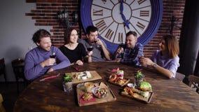 Un grupo de gente joven linda en un restaurante moderno en una tabla con bocados Cuecen a los hombres y a las muchachas con los v metrajes