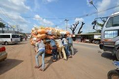 Un grupo de gente joven que empujaba un carro sobrecargó bolsos imagen de archivo libre de regalías