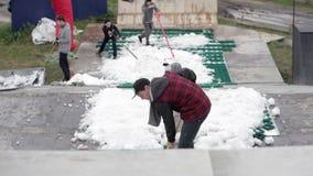 Un grupo de gente joven separó hacia fuera el traspaleo de nieve metrajes