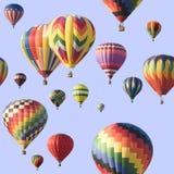Un grupo de globos de aire caliente coloridos que flotan a través de un cielo azul Imagen de archivo