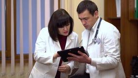 Un grupo de hablar de los doctores Mujeres y un hombre El doctor de sexo masculino guarda una tableta almacen de metraje de vídeo