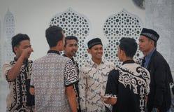Un grupo de hombres asiáticos musulmanes jovenes en camisas hermosas se está colocando cerca de las paredes de la mezquita foto de archivo