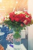 Un grupo de hombres de negocios está negociando en la oficina para la venta de flores en el fondo de un ramo grande de rosas colo foto de archivo libre de regalías