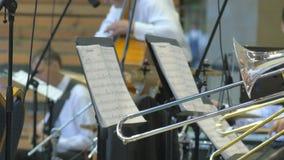 Un grupo de hombres que juegan en trambones en la etapa 4k de la persona anónima en el concierto instrumental almacen de metraje de vídeo