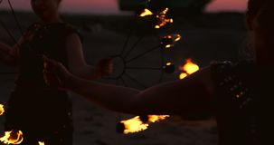 Un grupo de hombres y de demostración del fuego de la mujer en la noche en la arena almacen de video