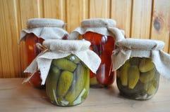 Un grupo de latas con los tomates y los pepinos conservados Fotografía de archivo