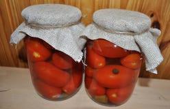 Un grupo de latas con los tomates y los pepinos conservados Imagen de archivo