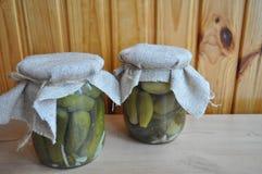 Un grupo de latas con los tomates y los pepinos conservados Foto de archivo