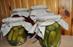 Un grupo de latas con los tomates y los pepinos conservados Foto de archivo libre de regalías