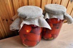 Un grupo de latas con los tomates y los pepinos conservados Fotos de archivo libres de regalías