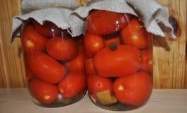 Un grupo de latas con los tomates y los pepinos conservados Imágenes de archivo libres de regalías