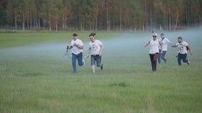 Un grupo de m?sicos de la roca que se divierten que corre con las herramientas en un campo humo-llenado tiro divertido almacen de video