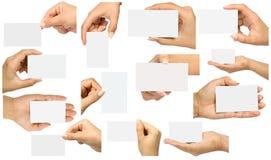 Un grupo de manos que sostienen tarjetas de visita en diversas posiciones Imagen de archivo