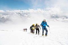 Un grupo de montañeses sube al top de una montaña coronada de nieve Imagen de archivo