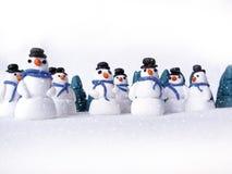 Un grupo de muñecos de nieve en la nieve Imágenes de archivo libres de regalías