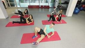 Un grupo de muchachas delgadas con el instructor de la aptitud trabaja con un coche en un gimnasio de la aptitud metrajes