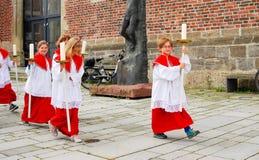 Un grupo de muchachos de altar procede a la iglesia Imagenes de archivo