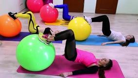 Un grupo de mujeres caucásicas jovenes que hacen ejercicios con los fitballs que ponen en un piso en un club de fitness almacen de video