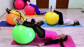 Un grupo de mujeres caucásicas jovenes que hacen ejercicios con los fitballs que ponen en un piso en un club de fitness metrajes