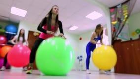 Un grupo de mujeres jovenes que hacen ejercicios con los fitballs en un club de fitness metrajes