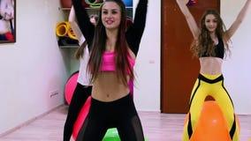 Un grupo de mujeres jovenes que hacen ejercicios con los fitballs en un club de fitness almacen de metraje de vídeo