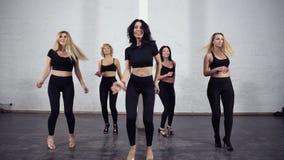 Un grupo de mujeres juguetonas atractivas en bachata activo negro del baile del desgaste en clase del salón de baile almacen de video
