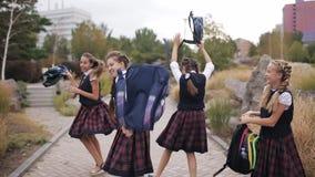 Un grupo de niños escuela-envejecidos después del día escolar que hacen el tonto y que se divierten en el parque almacen de video