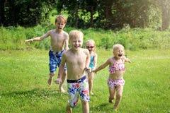 Un grupo de niños felices está sonriendo mientras que corren a través del exterior de la regadera en un día de verano imagen de archivo
