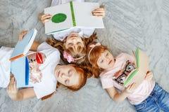 Un grupo de niños pone en el piso y lee los libros El conce Imagen de archivo libre de regalías