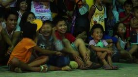 Un grupo de niños se sienta en piso de losa mientras que mira una competencia de la danza de la roca durante un evento del públic almacen de metraje de vídeo