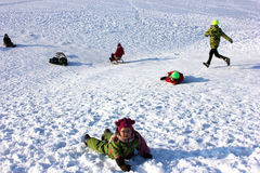 Un grupo de niños sledging Imagen de archivo libre de regalías