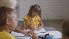 Un grupo de niños y un profesor dibujan en el Libro Blanco usando los lápices coloreados Alumnos primarios que dibujan en almacen de metraje de vídeo
