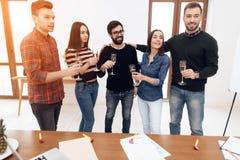 Un grupo de oficinistas jovenes que celebran imagenes de archivo