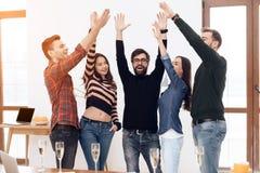 Un grupo de oficinistas jovenes que celebran foto de archivo