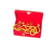 Un grupo de ornamento del oro en joyero rojo Foto de archivo libre de regalías