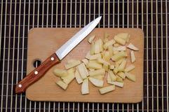 Un grupo de patatas cortadas en una tabla de cortar de madera con un sostenido fotografía de archivo libre de regalías