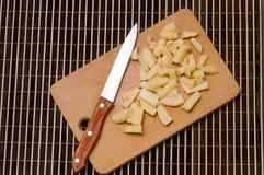 Un grupo de patatas cortadas en una tabla de cortar de madera con un sostenido imagenes de archivo